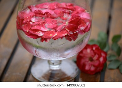 A lot of bright rose petals in cold water.A beautiful wine glass,water droplets on misted glass.A single rose is lying near on the wooden table Concept: Naturalism,ecology.Cosmetic body and face care