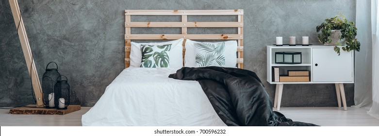 Bright scandinavian bedroom interior in minimalist design with wooden bedhead, black accessories and white bedside table