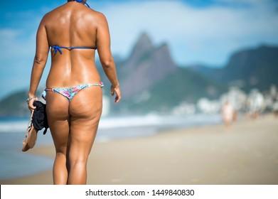 Bright scenic morning view of bikini beachgoers on Ipanema Beach with Two Brothers Mountain in Rio de Janeiro, Brazil