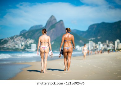 Bright scenic morning view of Two Brothers Mountain towering beyond beachgoers walking on Ipanema Beach in Rio de Janeiro, Brazil