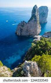 Bright scenic overlook of the dramatic Faraglioni rocks towering up from bright blue Mediterranean waters on the island of Capri, Italy