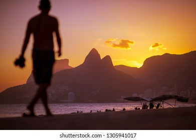Bright scenic view from the boardwalk at Arpoador of Ipanema Beach with Two Brothers Mountain in sunset silhouette in Rio de Janeiro, Brazil