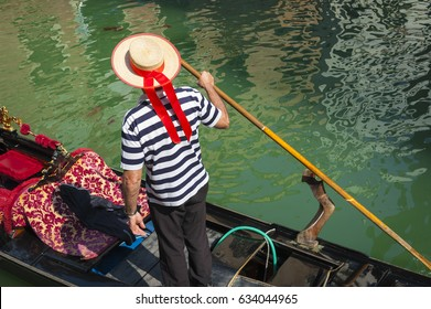 Bright scenic view of a classic Venetian gondola with ornate cushions and stripe-shirt gondolier on a canal in Venice, Italy