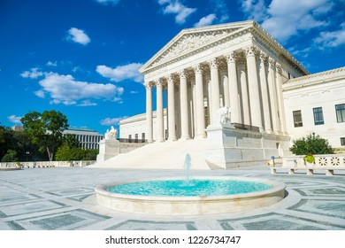 Bright scenic view of the neo-classical facade of the United States Supreme Court building from the plaza fountain under blue sky