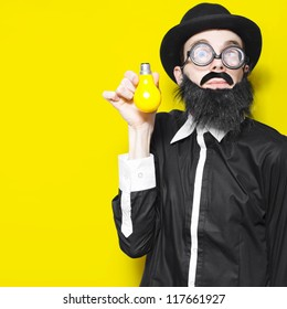 Bright Science School Teacher Standing Against Yellow Classroom Wall With Light Bulb In Hand, Depicting A Creative Idea