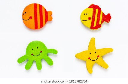 Bright sea creatures kids handmade figures set. Two fish, seastar and octopus. Flat wooden children's toys collection, white background isolated. A template for a collage of animated figures top view