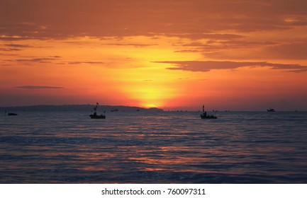 bright sea landscape with red sunset ,  the sea and the silhouette of the fishing boats