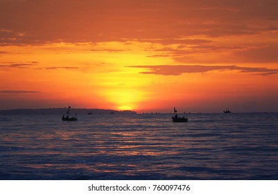 bright sea landscape with red sunset , sinm the sea and the silhouette of the fishing boats