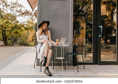 Bright, sensual girl with blond curls and in white summer sundress sits in cafe on the street, chatting in laptop