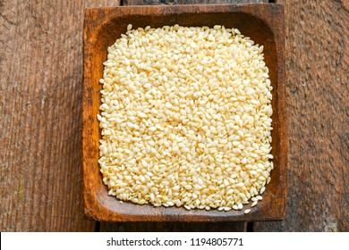 Bright sesame seeds in a wooden dish
