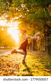 in the bright setting sunlight, the girl dancing with the hat and the plaything is on the road in autumn Park.