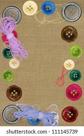 Bright sewing buttons and needles on gray fabric
