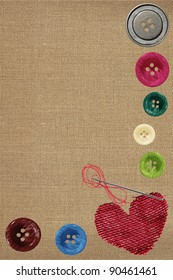 Bright sewing buttons, red textile heart and needle on gray fabric