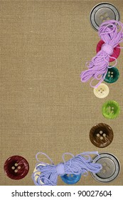 Bright sewing buttons and threads on gray fabric