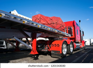 Bright shiny red classic bonnet American fancy big rig semi truck tractor with awesome stylish chrome accessories standing on truck stop with flat bed semi trailer caring covered commercial cargo