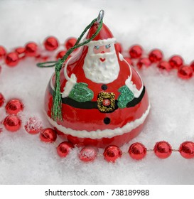A bright and shiny Santa Christmas tree decoration in the snow.