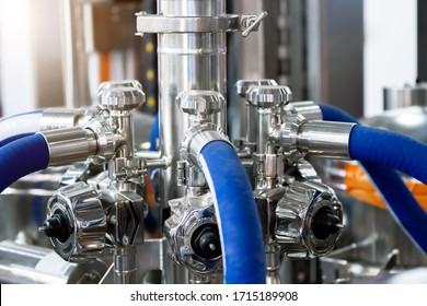 Bright shiny stainless steel piping. Distribution system of ball valves and metal piping, sensors and rubber hoses. Equipment for the food industry.