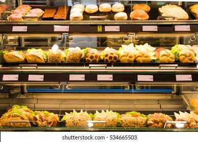Bright shot of burgers, donuts and sandwiches in a bakery or shop glass counter. Shiny showcase of baked fastfood with prices.