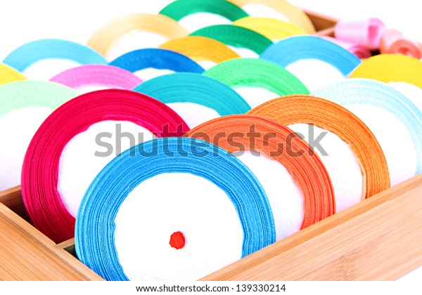 Bright silk ribbons in wooden box, close up