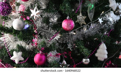 Bright silver and purple Christmas decorations with silver tinsel covering a pine tree