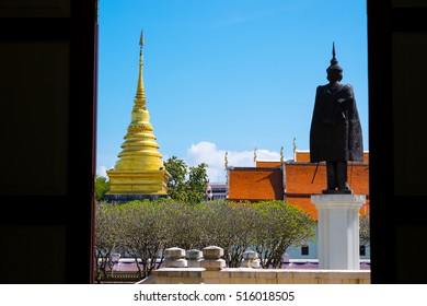 Bright sky with grass field in Nan Museum infront of golden pagoda in Wat Phra That Chang Kham, Nan,Thailand