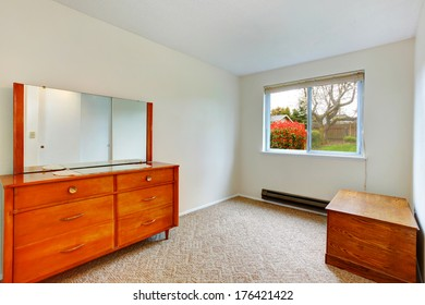 Bright small room with window. Room with beige carpet floor furnished with antique wooden chest and cabinet with mirror