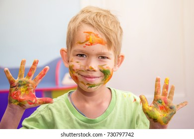 bright, smiling boy with a painted face and hands .