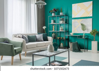 Bright sofa with many pillows standing next to a green armchair in living room interior with metal furniture and geometric paintings
