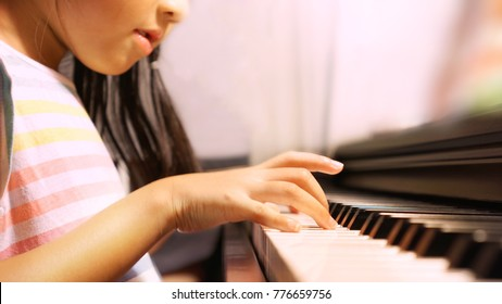 Bright, soft shot of Asian little girl happily playing keyboard piano during her practice at home