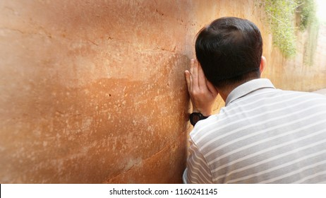 bright, soft shot of Asian man in an act of eavesdropping the conversations on the other side of the wall.