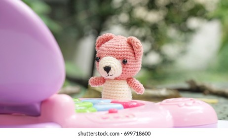 Bright, soft shot of cute pink crocheted bear doll playing a simple toy notebook in the garden in beautiful morning, implying fast learning of technology of children today