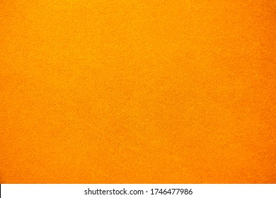 Bright solid color background. Empty orange surface with fine texture. Preparation for designer or layout
