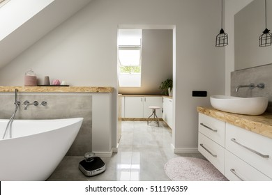 Bright, spacious bathroom with big, oval bathtub, white amenities and modern weight on the floor