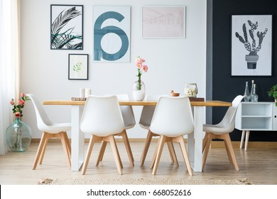 Bright spacious dining room with flowers and posters