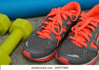 Bright sport shoes with dumbbell and yoga mat