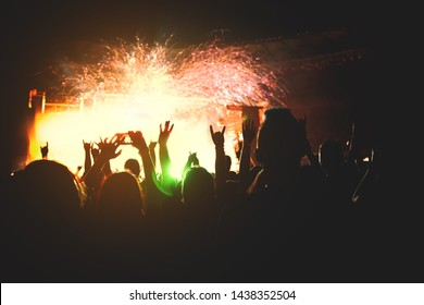 The bright spotlight shines on the dancing people. The audience applauds the musicians. Silhouette of a concert crowd.