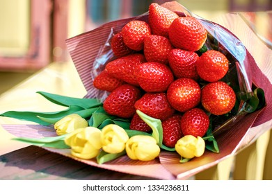 bright spring bouquet of tulips and strawberries. Edible bouquet for mother's day and March 8