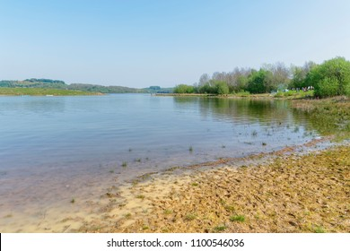 A bright spring day on the banks of Carsington Resevoir in Derbyshire. Low water levels reveal a muddy shoreline.