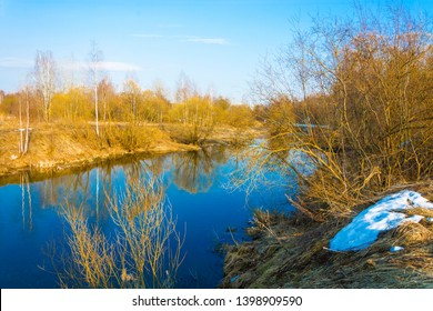 Bright spring landscape with a small river and blue sky in the yellow rays of the setting sun.