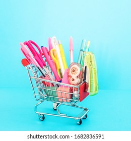 Bright stationery objects in mini supermarket cart on white background. Back to school concept.