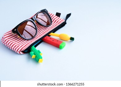Bright stationery pens in the form of a cactus, watermelon, pineapple in a pencil case and sunglasses on a blue background. Back to school. Top view.