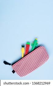 Bright stationery pens in the form of a cactus, watermelon, pineapple in a pencil case on a blue background. Back to school. Top view.