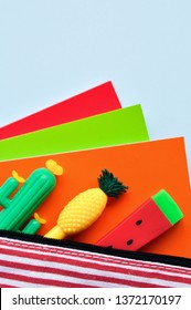 Bright stationery pens in the form of a cactus, watermelon, pineapple in a pencil case and colored notebooks on a blue background. Back to school. Top view.