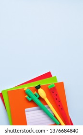 Bright stationery pens in the form of a cactus, watermelon, pineapple and colored notebooks on a blue background. Back to school. Top view.