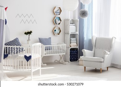 Bright and stylish nursery with white chair, crib and cradle