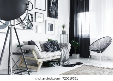 Bright stylish room with metal furniture and wooden couch with handmade pillow