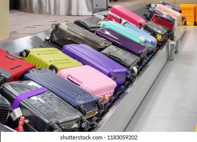 Bright suitcases on luggage conveyor belt at arrival area of passenger terminal in airport. View of baggage carousel.