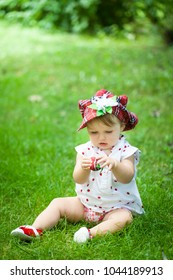 Bright summer berry party in park. Cute little girl in red cap on the grass