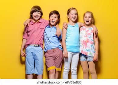 Bright summer children. Group of joyful children posing together over bright yellow background.