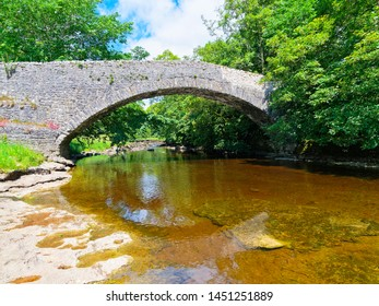 A bright summer day besides the River Ribble near an old stone bridge in the Yorkshire Dales
